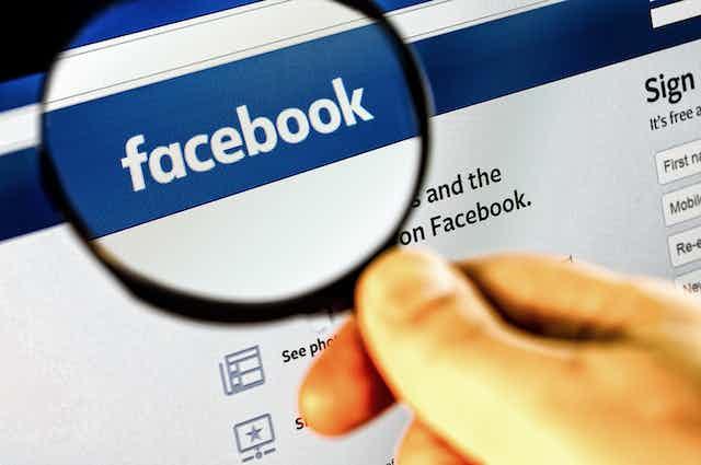 Lupa ampliando el logotipo de Facebook.