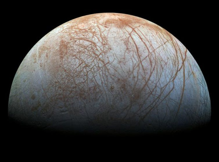 Jupiter's white with brown streaks moon Europa in space,