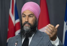 NDP Leader Jagmeet Singh responds to a question as he gestures and stands behind a podium.
