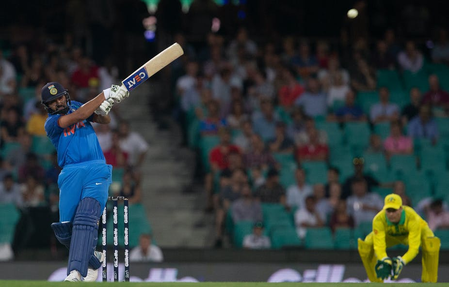 Rohit Sharma hits cricket ball with man crouching behind.