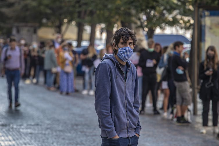 A man in a mask standing in front of a long queue of people, also in masks.