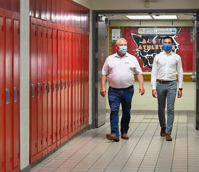 Premier Doug Ford and Education Minister Stephen Lecce, casually dressed in jeans, white shirts and blue face masks, walk beside a row of red lockers.
