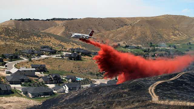 Tanker dropping fire retardant on scorched hillside in suburban Boise