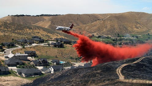 Tanker dropping fire retardant on scorched hillside in suburban Boise