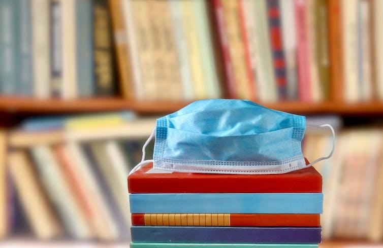 Mascarilla quirúrgica sobre una pila de libros.