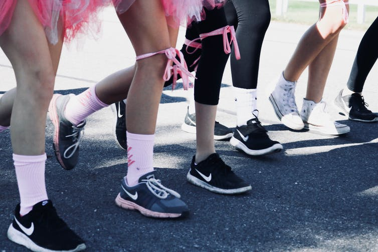 Close up of legs wrapped in pink ribbons waiting to start a race