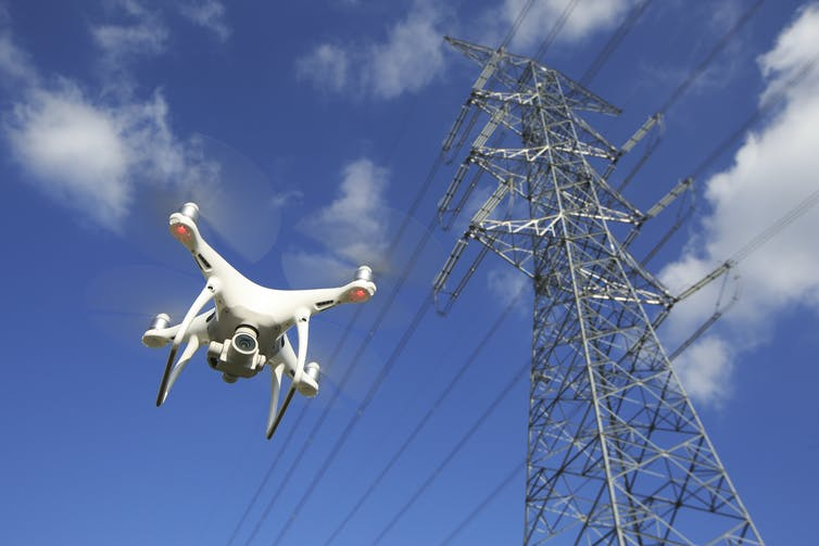Drone hovers near electricity pylon