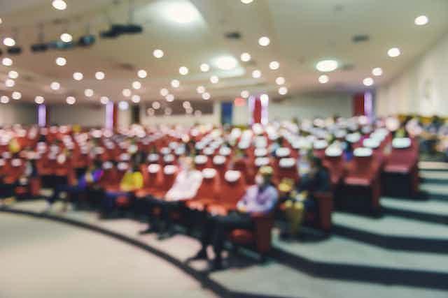 foto borrosa de un salón de actos con personas sentadas con distancia de seguridad y mascarillas.