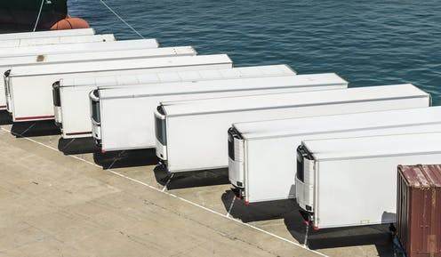 A line of freezer trucks parked on a dock.