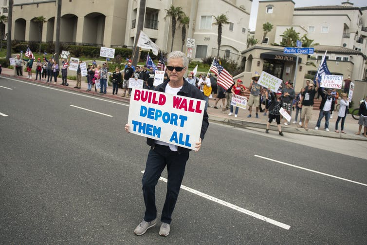 An anti-immigration protester stands in the street holding a sign that reads, 'Build Wall Deport Them All'