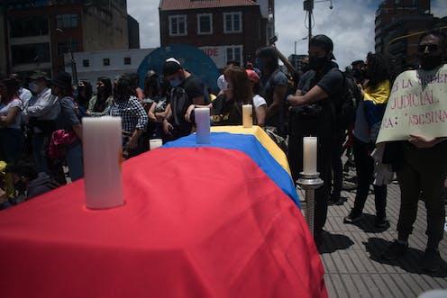 Ataúd cubierto por la bandera de Colombia y tres velas.
