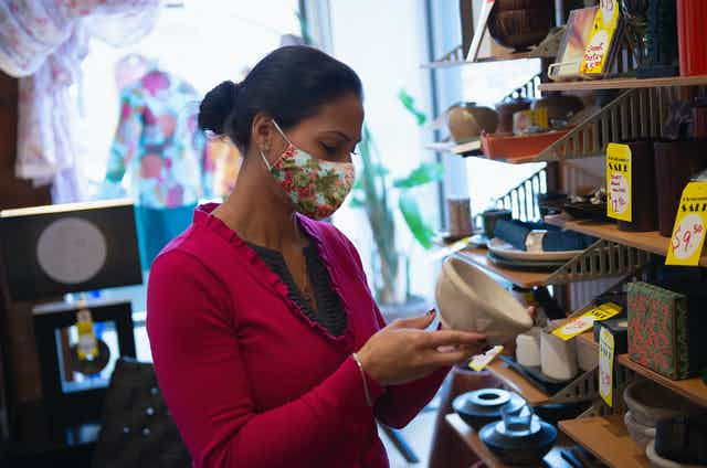 A woman wearing a mask looks at a bowl.