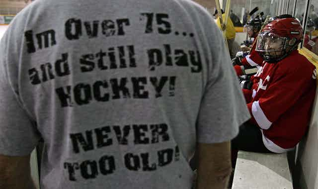 A man at a hockey rink wears a t-shirt that says I'm over 75...and still play HOCKEY! NEVER TOO OLD!