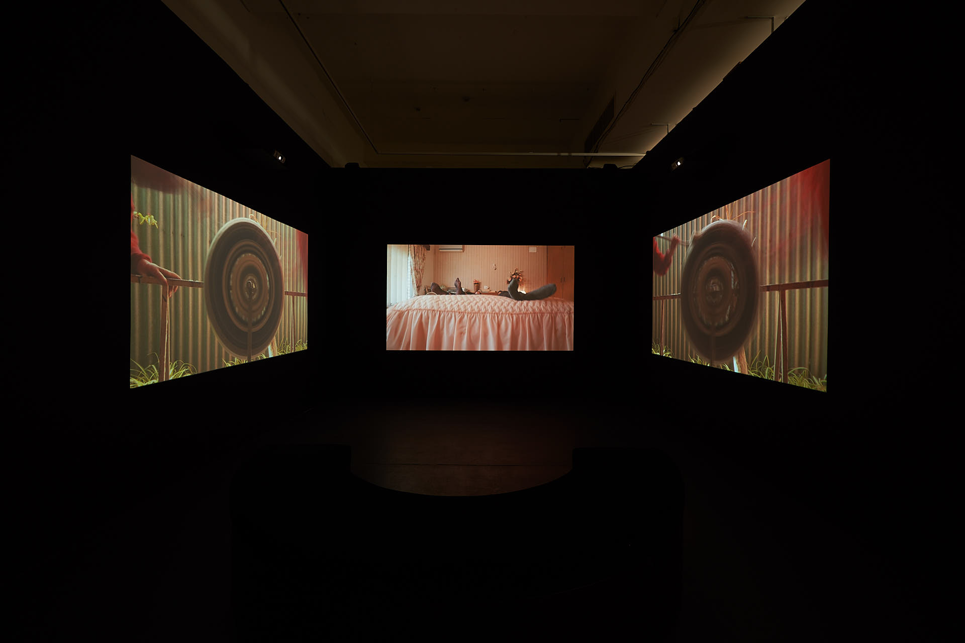 Video projected onto three screens in a black room