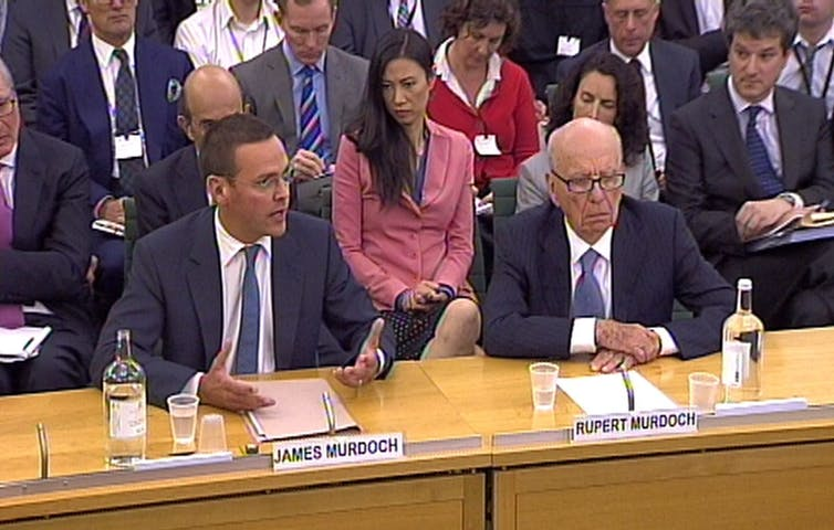 Two men in suits sit behind a wooden desk, giving evidence.