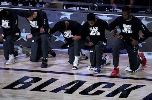 basketball players kneeling on court