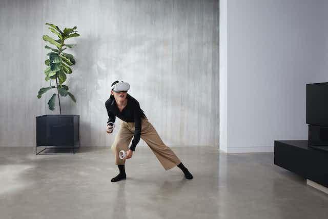 A woman wears a virtual reality headset in a minimalist office setting.