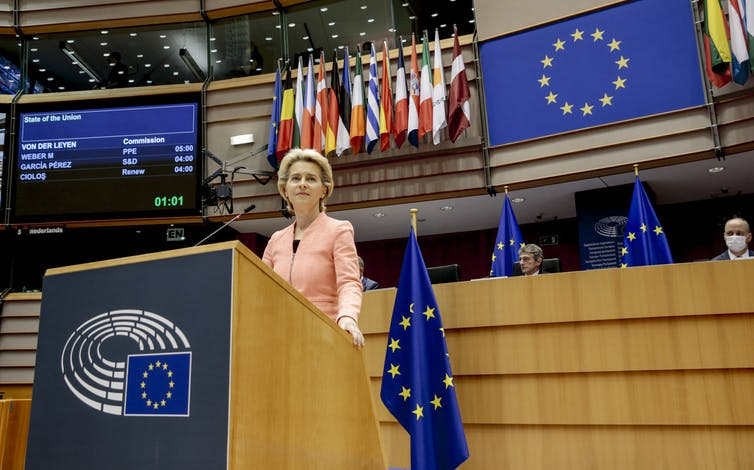 The European Commission president speaking at the European Parliament in front of EU and national flags.