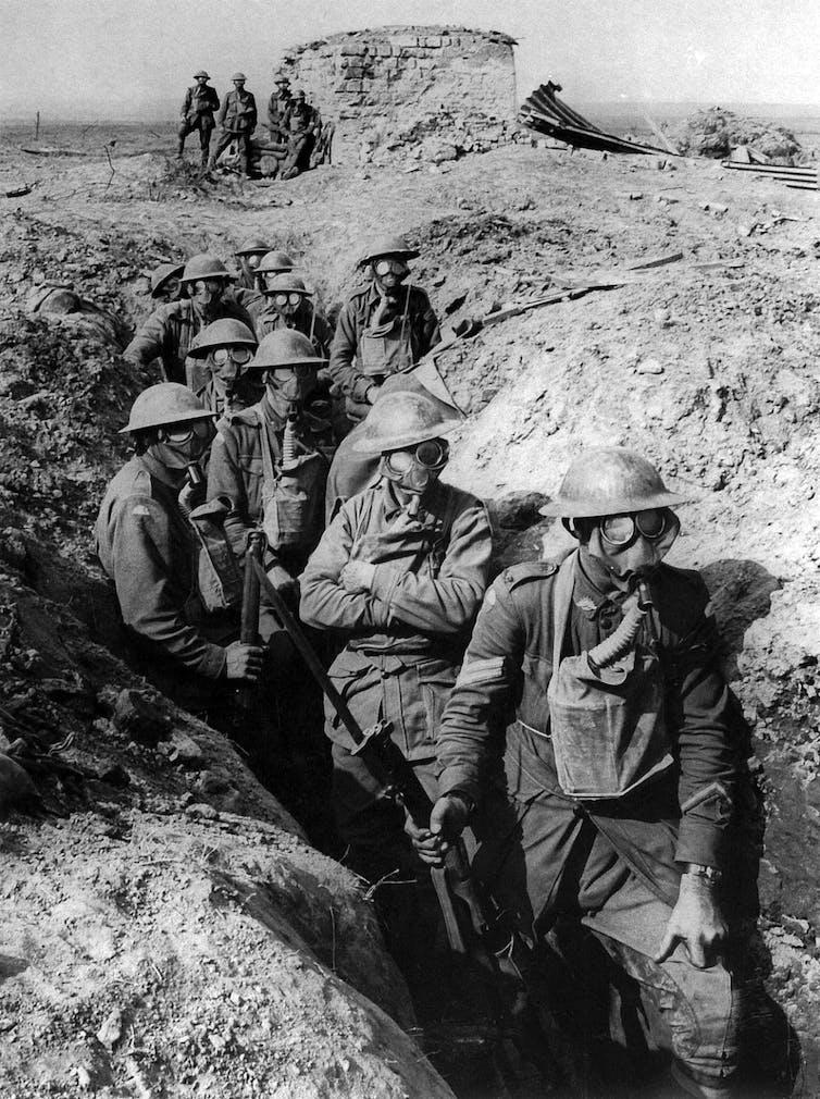 Foto en blanco y negro de soldados en una trinchera durante la primera guerra mundial con máscaras antigás.
