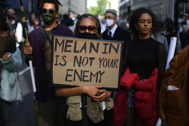 Black Lives Matter protestors in New York, a woman in sunglasses in the foreground holding a placard that reads, 'Melanin is not your enemy'