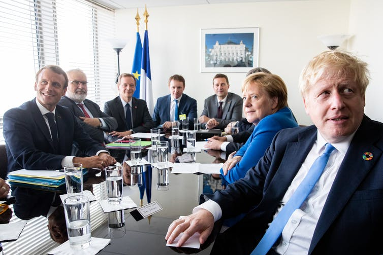 Emmanuel Macron, Angela Merkel and Boris Johnson sit at a table with diplomats.