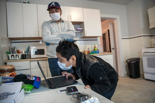A boy in a mask stares into his laptop while his father looks on.
