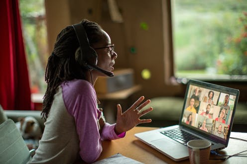a woman wearing a headset in a home Speaks and gestures in front of an open laptop displaying a video conference