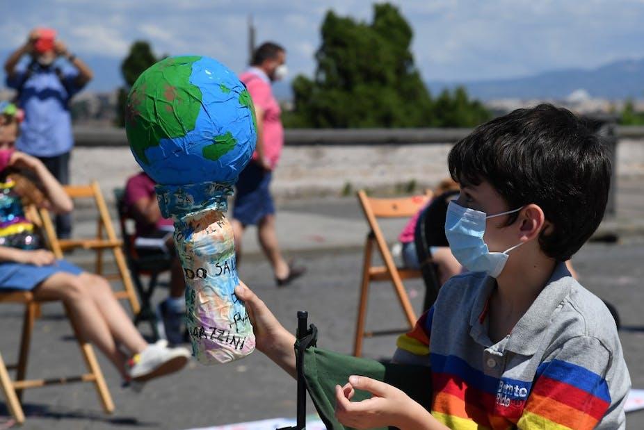 Un jeune garçon en masque sanitaire tient une représentation de la Terre en papier mâché