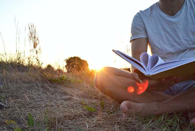 Una persona descalza leyendo ante una puesta de sol. Las hojas del libro forman un corazón.