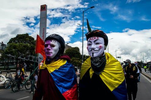 Dos manifestantes con máscaras y sendas banderas de Colombia atadas al cuello.