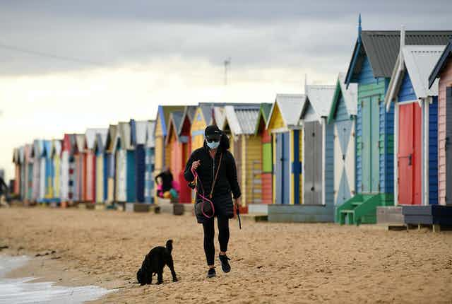 A person walking their dog on the beach wearing a mask
