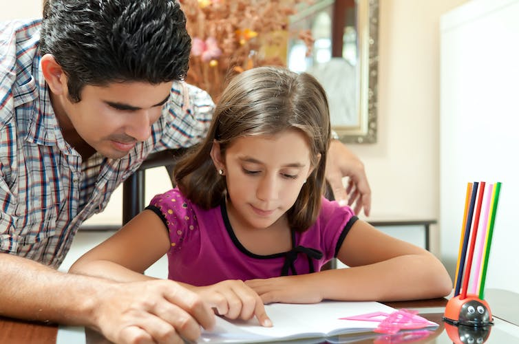 Father helping his daughter with schoolwork
