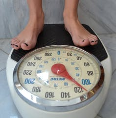 A woman's feet standing on a scale that reads about 51 kilograms.