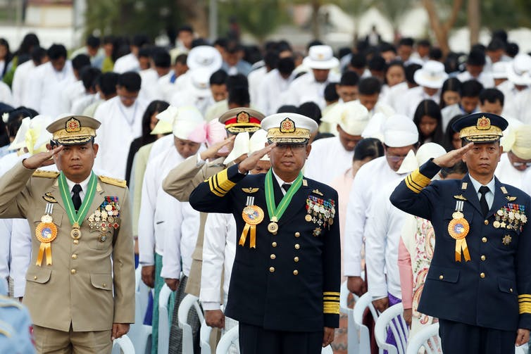 Myanmar military officers salute at their national flag during a ceremony.