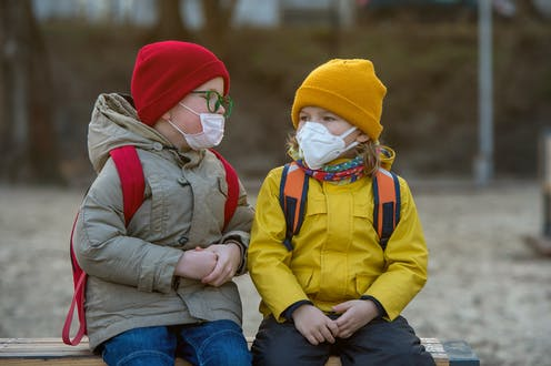 Two young children in masks on a bench.