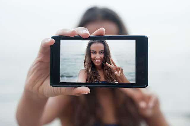 Rostro de una chica en un teléfono móvil mientras se hace una foto a sí misma.