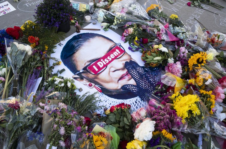 Photo of Ruth Bader Ginsburg on pavement surrounded by flowers.