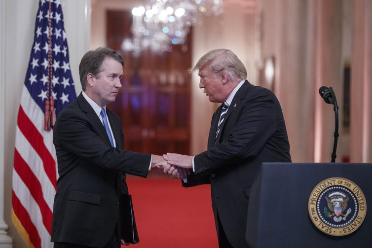 Donald Trump shakes hand of Brett Kavanaugh with US flag behind.