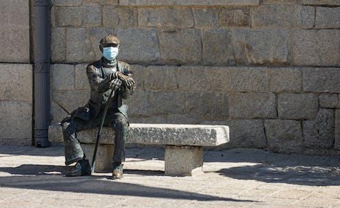 Estatua de un hombre sentado en un banco al que han colocado una mascarilla quirúrgica