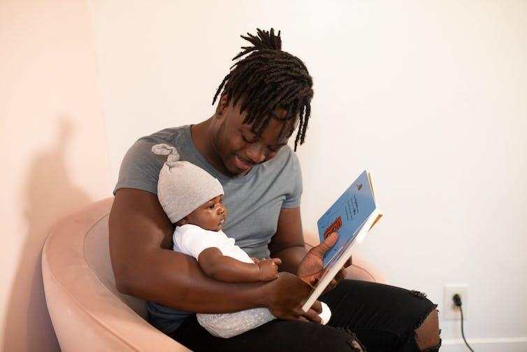 Un jeune père lit une histoire à son bébé
