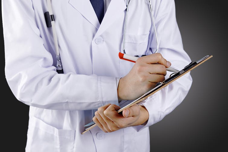 Researcher in a white lab coat writing on a clipboard.