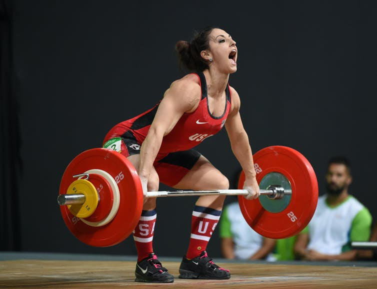 Female olympic weightlifter performing a deadlift.