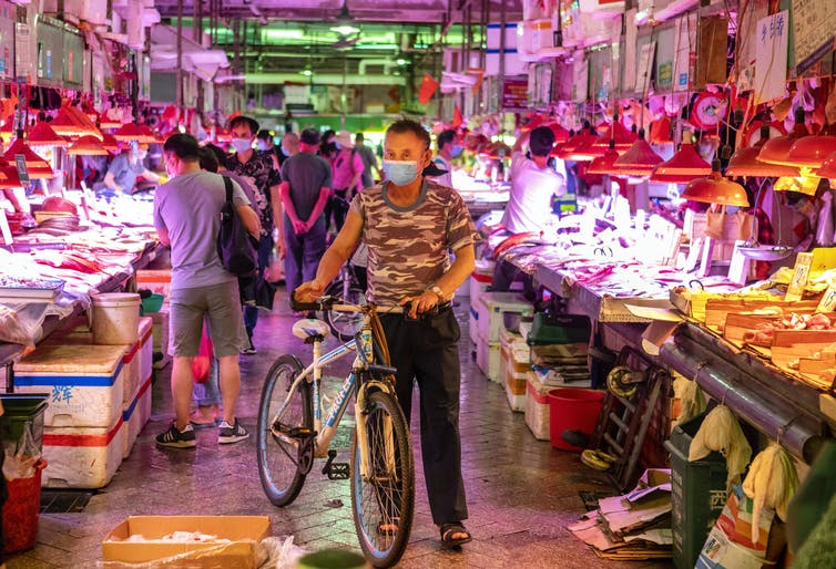 A man with a bicycle, wearing a face mask, standing in a Chinese wet market