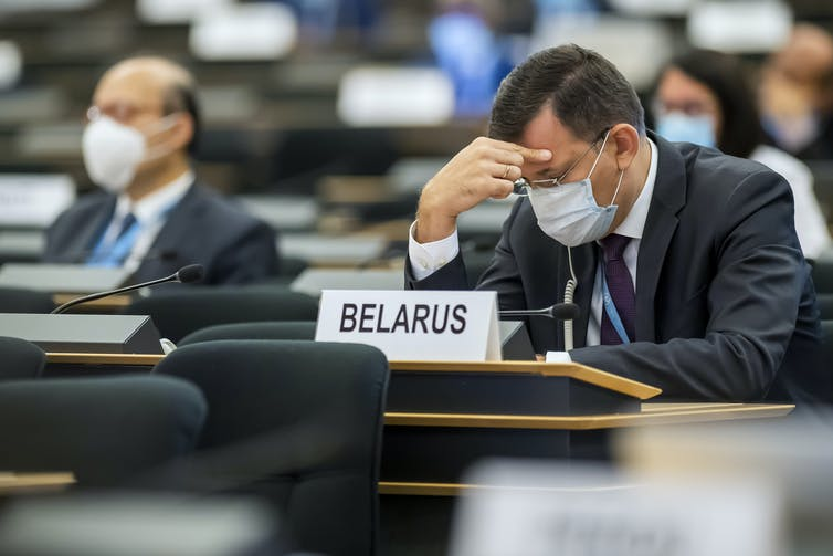 Man in maks holds head in hand in front of sign saying Belarus.