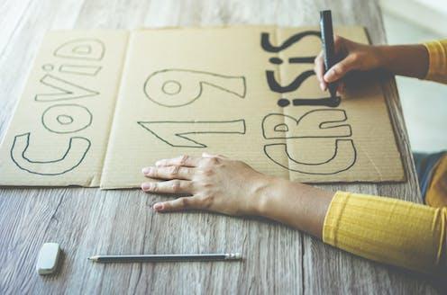 Una persona elabora una pancarta de cartón en la que se lee: Covid 19 crisis
