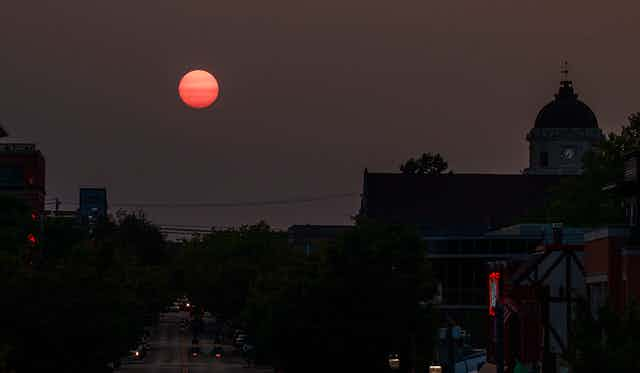 A red sun setting over a town with a clocktower.