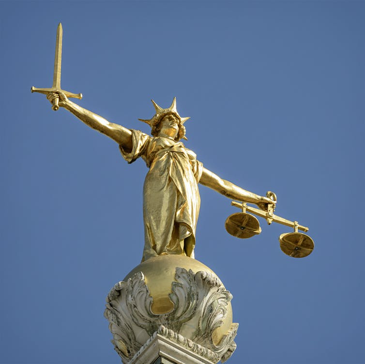 A statue of Lady Justice with a sword in one hand and scales in the other.