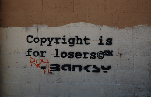 """Wall at 244 Water Street NYC showing Banksy graffiti that says """"Copyright is for losers""""."""""""