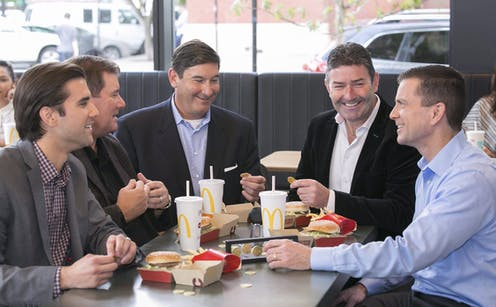The former CEO of McDonald's is seated at one of the food chain's restaurants while he and others eat Big Macs.