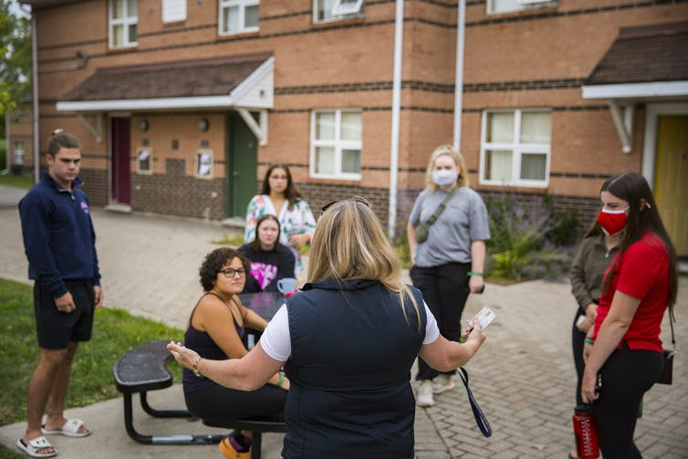 A person presents to a semi-circle of masked students standing outdoors.